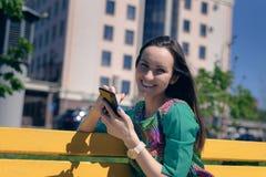 Nette lächelnde Frau auf einer gelben Bank mit einem Smartphone, der die Kamera betrachtet lizenzfreies stockbild