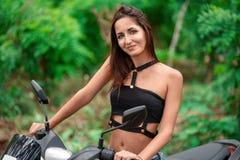 Nette lächelnde Frau, die das Rad eines Mopeds auf einem natürlichen grünen Hintergrund hält lizenzfreie stockfotos