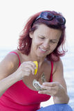 Nette lächelnde Frau, die frische Auster isst Stockbild