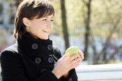 Nette lächelnde Frau im Park mit Apfel stockbild