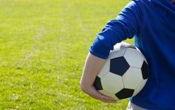 Nette lächelnde glückliche 8 Jahre alte Jungenstand mit Volleyballball auf dem Parkgebiet draußen am sonnigen Sommertag Stockfoto