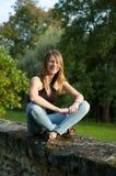 Nette lächelnde junge Frau, die im Park während des Sonnenuntergangs in den Jeans und im schwarzen Hemd sitzt und die Kamera betr Stockfotos