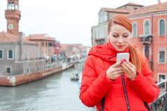 Nette lächelnde Latina-Frau, die intelligentes Telefon in Venedig Italien verwendet stockfoto
