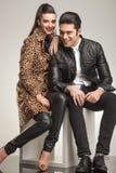 Nette lächelnde Modepaare beim Sitzen auf einem weißen Würfel Lizenzfreies Stockfoto