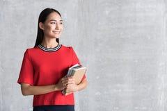 Nette lächelnde tragende Notizblöcke der Frau stockfoto