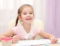 Nette lächelnde Zeichnung des kleinen Mädchens mit Farbe und Malerpinsel Stockfotografie
