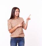 nette lateinische Dame 20s, die nach links ihr zeigt Lizenzfreies Stockbild