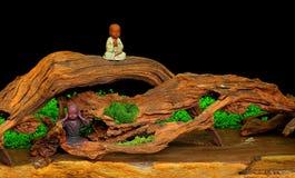 Nette Lehmstatuen von zwei kleinen meditierenden Mönchen Stockfotografie