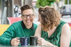 Nette lesbische Paare, die draußen an den Bistros scherzen stockbilder