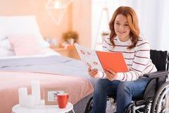 Nette Lesung der behinderten Frau im Rollstuhl Lizenzfreies Stockbild