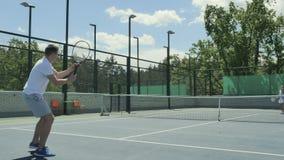 Nette Leute, die Tennis auf dem Tennisplatz spielen stock footage