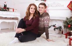 Nette Liebespaare auf Teppich Frau und Mann, die Weihnachten feiern Lizenzfreies Stockbild