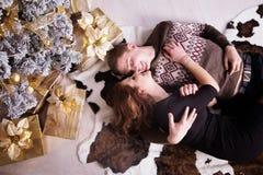 Nette Liebespaare auf Teppich Frau und Mann, die Weihnachten feiern Lizenzfreie Stockbilder