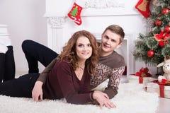 Nette Liebespaare auf Teppich Frau und Mann, die Weihnachten feiern Lizenzfreie Stockfotografie