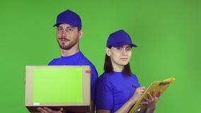 Nette Lieferungsarbeitskräfte mit einem Paket lächelnd zur Kamera lizenzfreie stockfotos