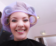 Nette lustige blonde Mädchenhaarlockenwicklerrollen durch haidresser im Schönheitssalon Lizenzfreie Stockfotos