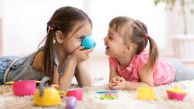 Nette lustige Kinder, die zu Hause mit Spielwaren spielen lizenzfreies stockbild