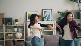 Nette Mädchen in den modischen Jeans tanzen zu Hause Musik zusammen hören und Haben des Spaßes Gemischtrassige Freundschaft stock footage