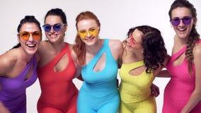 Nette Mädchen, die in der bunten Kleidung lachen und aufwerfen stock video