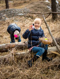 Nette Mädchen, die Ostereijagd am Wald an kaltem April-Tag haben Stockfotografie