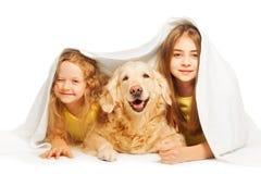Nette Mädchen, die unter der weißen Decke mit Hund sich verstecken Lizenzfreies Stockfoto