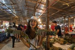 Nette Mädchen-Griff-Ananas, die auf tropischem Straßenmarkt- im junge Frauen-Touristen Thailands kauft frische Früchte kaufen Lizenzfreie Stockbilder