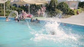 Nette Mädchen im Bikini, der in das Pool und im Lachen springt stock footage