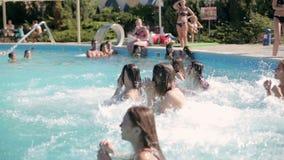 Nette Mädchen im Bikini, der in das Pool und im Lachen springt stock video