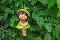 Nette Mädchenlächeln-Lehmpuppen im Garten Stockfotografie