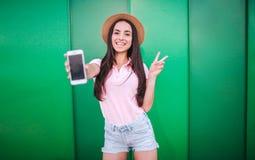 Nette Mädchenstände und -haltungen auf Kamera Sie hält weißes Telefon in der Hand und showes bessern Symbol mit dem anderen aus F lizenzfreies stockbild