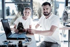 Nette Männer, die an neuer Robotermaschine arbeiten lizenzfreies stockbild