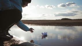 Nette M?dchenspiele mit dem Papierschiff in einem See zur Sonnenuntergangzeit Kindertraum und Reisekonzept, Lebensstil stock footage