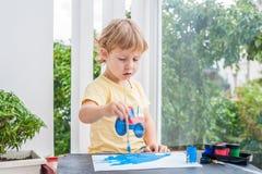 Nette Malerei des kleinen Jungen mit bunten Farben Stockfotos