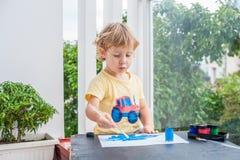 Nette Malerei des kleinen Jungen mit bunten Farben Lizenzfreie Stockfotos