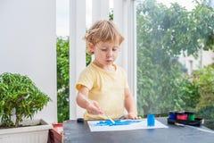 Nette Malerei des kleinen Jungen mit bunten Farben Stockfotografie