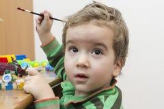 Nette Malereidinosaurier des kleinen Jungen am Schreibtisch Stockbild