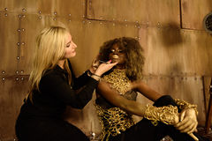 Nette Maskenbildnermalereilippen zum Modellieren an der Fotoaufnahme auf Boden im Studio des strahlenden Golds Lizenzfreies Stockbild