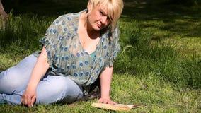 Nette Modefrau liegt auf grünem Gras und dem Ablesen eines interessanten Buches im Stadtpark am Sommertag stock video