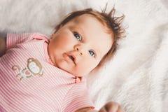 Nette 3 Monate alte Baby im Rosa, das sich zu Hause auf einem weißen Bett betrachtet Kamera hinlegt Große wachsame Augen Säugling Stockfotografie