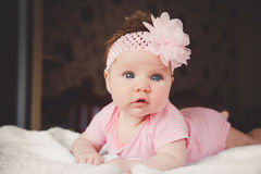 Nette 3 Monate alte Baby im Rosa, das sich zu Hause auf einem weißen Bett hinlegt Große wachsame Augen Kind, das im Bett Nickerch Stockbild