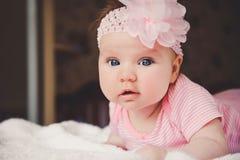 Nette 3 Monate alte lächelnde Baby im Rosa, das sich zu Hause auf einem weißen Bett betrachtet Kamera hinlegt Große wachsame Auge Stockfotografie
