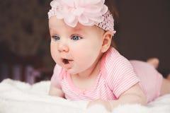 Nette 3 Monate alte lächelnde Baby im Rosa, das sich zu Hause auf einem weißen Bett hinlegt Große wachsame Augen Kind, das im Bet Lizenzfreie Stockfotos