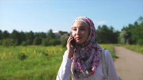 Nette moslemische Frau, die mit Freund auf Mobile während des Wegs spricht stock video footage