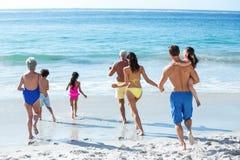 Nette multi Generationsfamilie, die in das Meer läuft Lizenzfreies Stockbild