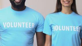 Nette multiethnische Freiwillige, welche die Hände untersuchen Kamera, Hilfe kreuzen stock footage