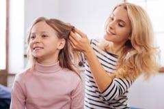 Nette Mutter, die eine Frisur für ihre kleine Tochter macht Lizenzfreies Stockbild