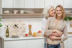 Nette Mutter, die ihr erwachsenes Kind in der Küche umfasst Stockbild