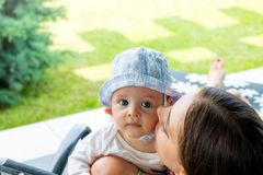 Nette Mutter, die reizendes blauäugiges Baby küssend umarmt, streichelt und Backe lizenzfreies stockbild