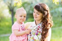 Nette Mutter mit Baby draußen Stockbilder