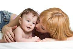 Nette Mutter umfasst ihr kleines Baby Frau und neugeborener Kinderjunge entspannen sich in einem weißen Schlafzimmer Lizenzfreie Stockfotos